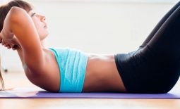 Mixed-race-woman-doing-sit-ups-on-yoga-mat