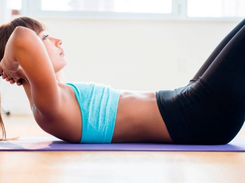 Mixed-race-woman-doing-sit-ups-on-yoga-mat